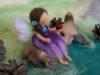 Fairy with ladybug on a root installation